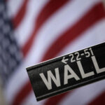 The Wall Street sign hangs in front of the American flag on the facade of the New York Stock Exchange Thursday, July 23, 2009 in New York. Investors celebrated news of another jump in home sales by propelling the Dow Jones industrials to their first close above 9,000 since January. (AP Photo/Mary Altaffer)